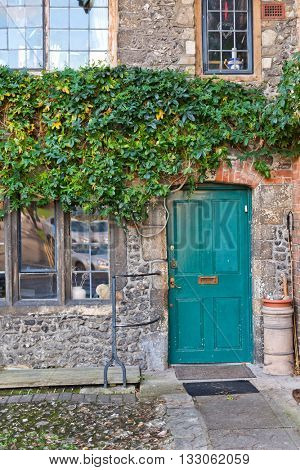 WINCHESTER, UK - FEBRUARY 07, 2016: Colorful turquoise blue wooden entrance door in an old stone building with a green creeper trailing over the wall. Winchester, UK on February 08, 2016.