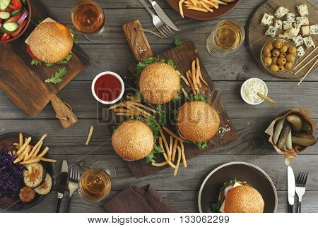 Different food on a wooden table burgers fries grilled eggplant salad pickles sauces roquefort cheese olives and wine top view. Outdoors food Concept