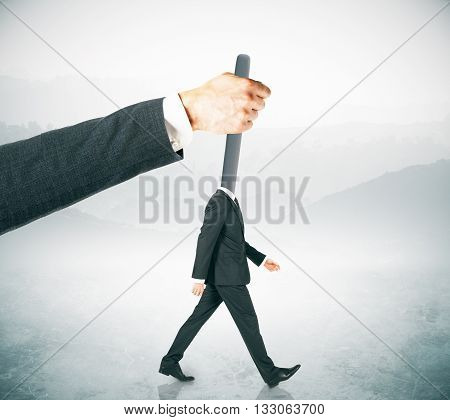 Hand manipulating lever-headed businessman on abstract foggy background. Concept of control
