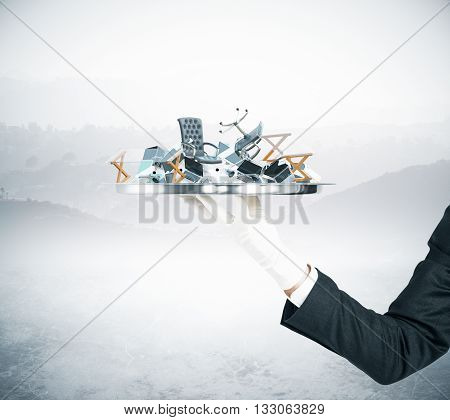Businessman hand holding tray with office tools and furniture on abstract ladscape background