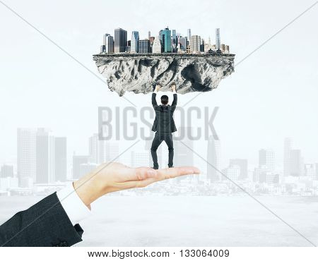 Businessman miniature standing on hand and upholding abstract city on foggy background
