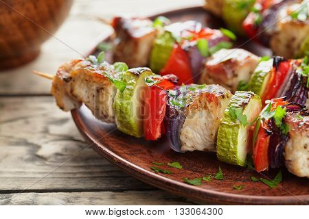 Grilled marinated turkey or chicken meat shish kebab skewers with ketchup sauce, chopped parsley and tomatoes on rustic wooden table background. Traditional barbecue grill food