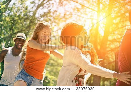 Multiracial friends dancing in garden party during summer time