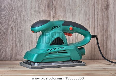 Electric sanding machine for home handyman use on wooden background close up.