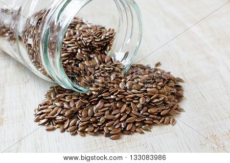 flaxseed spilled from a glass jar on a wooden board