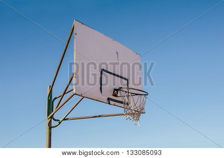Close-up of deteriorated basketball circle against of blue sky