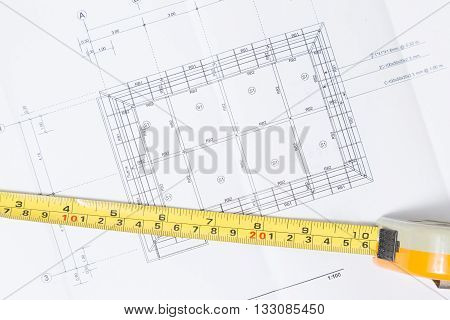 A tape measure over a construction plan drawing