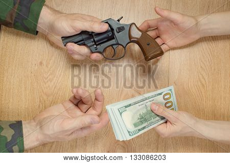 Transfers of money in exchange for a gun under certain conditions sitting at the table.