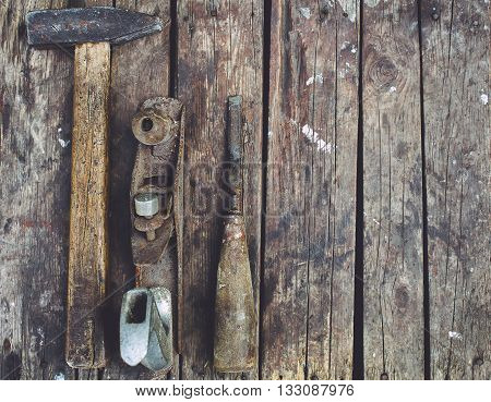 Old woodworking tools lie on a wooden surface. Hammer planer chisel.
