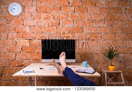 Feet Of Businessman, Sitting At Office Desk, Brick Wall