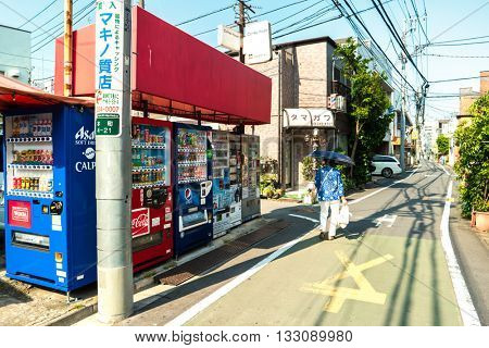 Tokyo - May 2016: Small lane with vending machines and lady with umbrella.