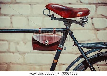 Photo old vintage bike which stands near the brick wall. Close up of an old worn-out bicycle frame in which leather vintage shabby brown seat glove compartment. Behind is the trunk.