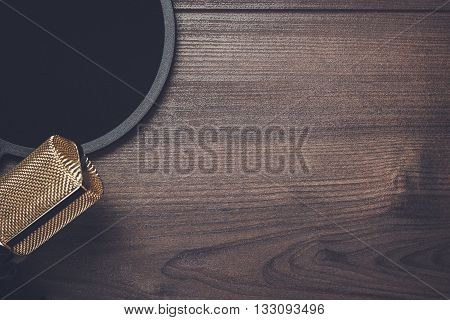 vintage condensing microphone and pop filter over wooden background