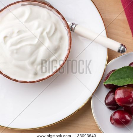 Overhead Square view of thick creamy natural greek yoghurt with summer fruit healthy breakfast meal set on the table. The diet breakfast includes a home made yoghurt Diet and health concepts.