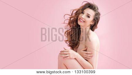 Naked brunette beauty over pink background