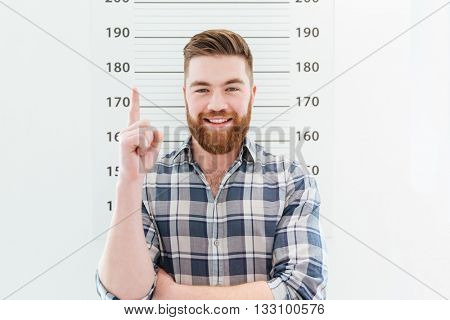 Mugshot of a smiling man pointing finger up