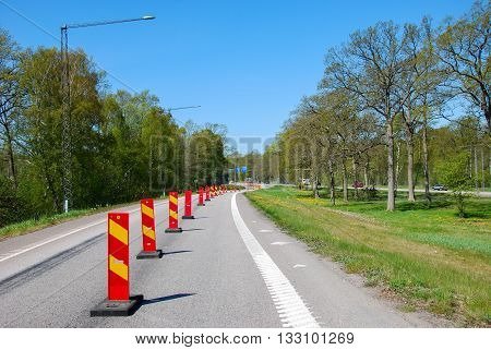 Roadblocks in a row on a road by springtime