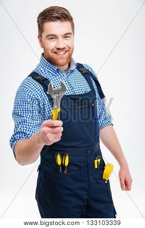 Smiling male builder holding wrench isolated on a white background