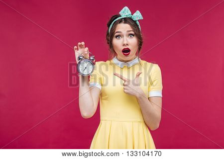Cute amazed pinup girl pointing on alarm clock over pink background