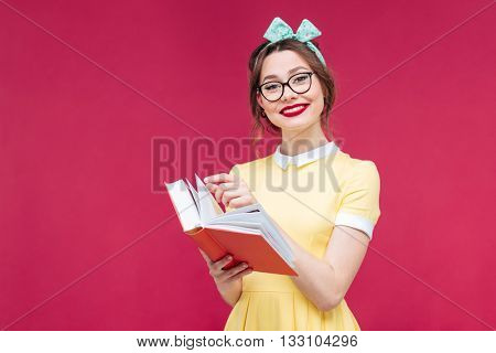 Smiling cute pinup girl in glasses holding red book over pink background
