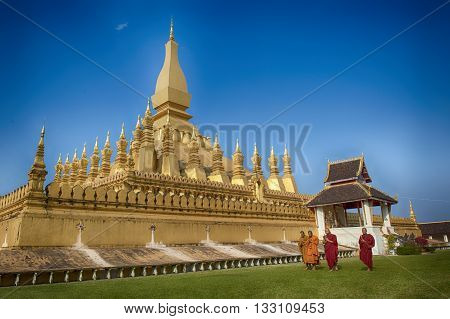VIENTIANE LAOS - JANUARY 19 2012: Buddhist monk praying and walking around Wat Phra That Luang in Vientiane Lao PDR