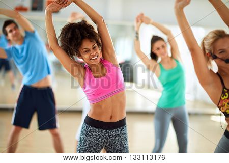 Young black female doing stretching exercises in group on fitness class
