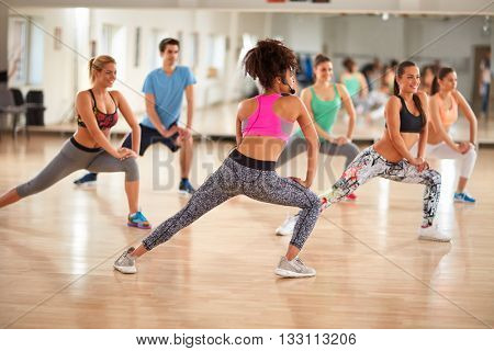 Young group of fitness exercisers in colorful sport clothes with female instructor in fitness class