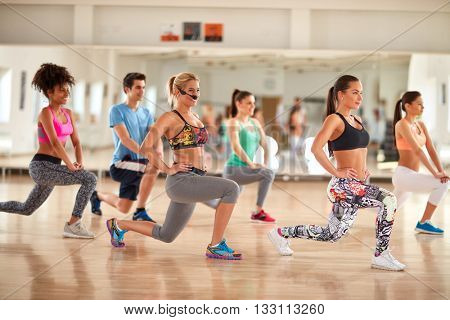 Group of young people doing exercises for legs and breech in gym