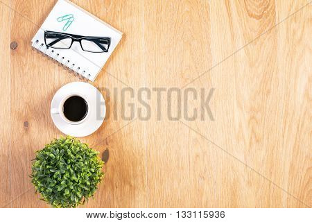Top view of wooden desktop with coffee cup plant glasses notepad and clips. Mock up poster