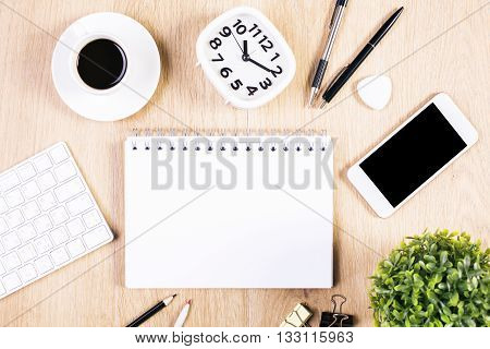 Top view of blank spiral notepad on tabletop with smart phone coffee cup keyboard clock and other stationery items. Mock up