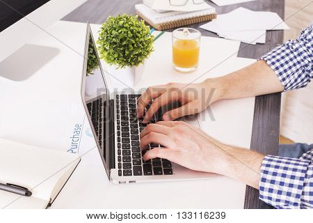 Sideview of businessman hands typing on laptop keyboard placed on office desktop with various items