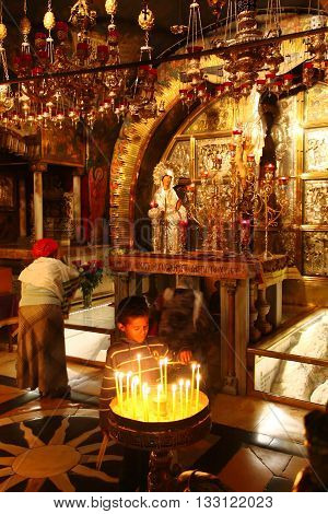 JERUSALEM OLD CITY, ISRAEL, 1 APRIL 2013. Editorial Photograph of Young Child Lighting Candles at The Golgotha Altar in the Church of the Holy Sepulchre, widely believed to be the site of Jesus Christ's crucifixion