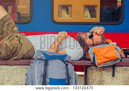 Handsome male backpacker tourist napping on a bench and baggage at the station