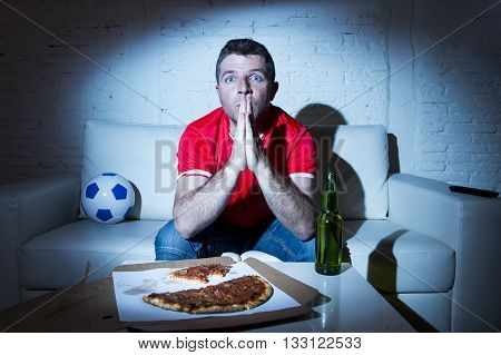 crazy fanatic man football fan watching football game on television wearing red team jersey suffering nervous and stress praying god on sofa couch at home with soccer ball beer bottle and pizza
