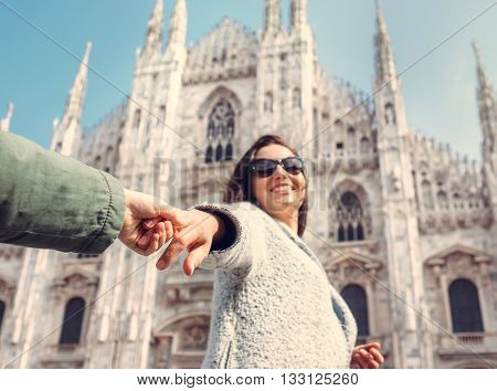 Mother with son take with hands and run together to Duomo di Milano