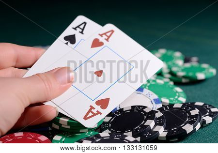 Casino chips and pair of aces in a woman's hand.