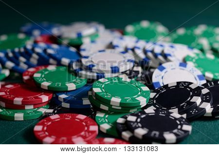 Stack of casino chips on a green background. Poker theme