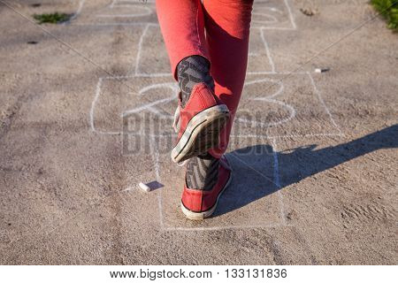 young girl in red sneakers starts playing hopscotch game