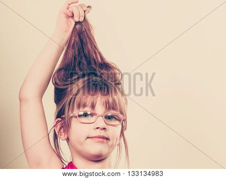Play and fun. Charming little girl making funny crazy hair. Smiling lovely cute female child wearing glasses. Positive facial emotion.