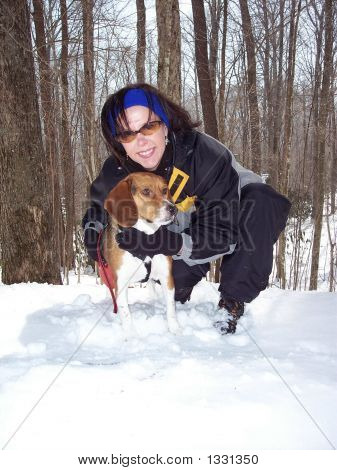 a woman hugs her dog in the snow. poster