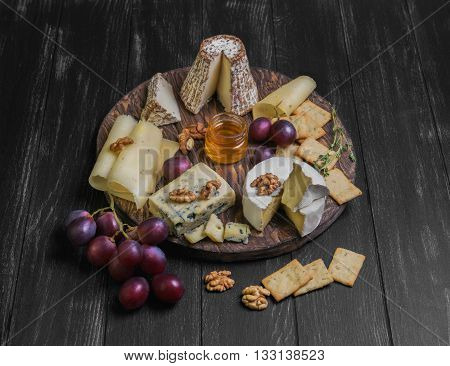 Assorted Cheeses On Round Wooden Board Plate