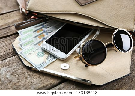 Woman's purse with glasses, phone and money on wooden background