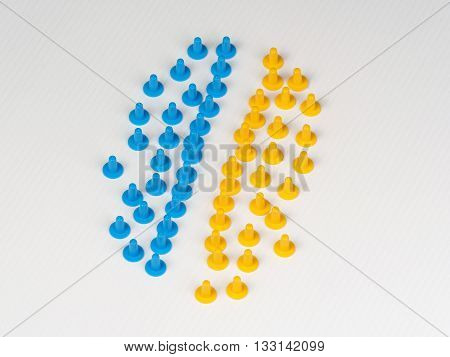 Two groups facing each other illustrated by colored plastic board game hats in various colors