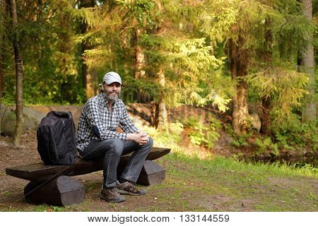 Mature man with backpack resting on the bench in the park
