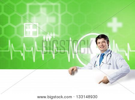 Young handsome doctor holding white blank banner. Place your text
