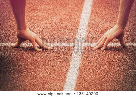 Hands on the starting line of a track and field running race