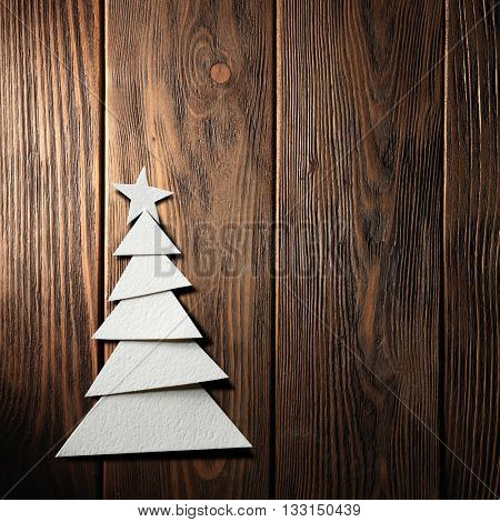 Christmas tree cut out from paper on a wooden background