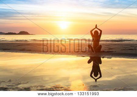 Woman doing meditation near the ocean. Yoga and health.