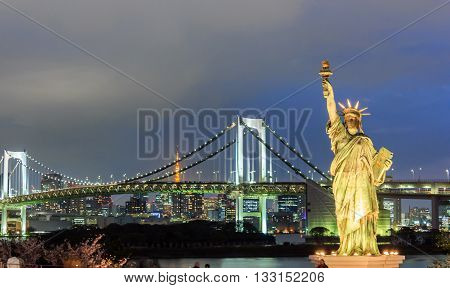 Lady liberty juxtaposed stand at Odaiba and Rainbow Bridge at Odaiba. Japan.