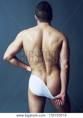 back of a handsome muscular sporty man against dark studio background
